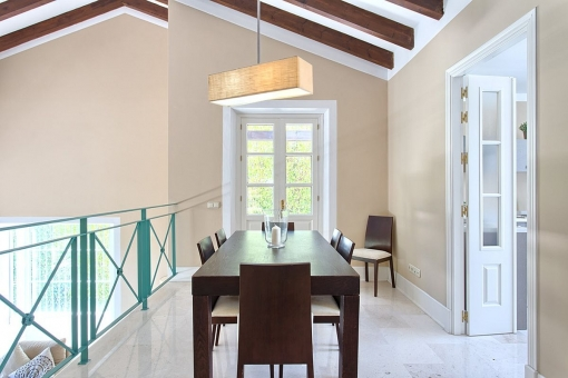 The dining area with wooden table and access to the kitchen