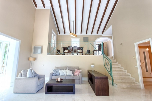 The staircase to the dining area with wooden beams