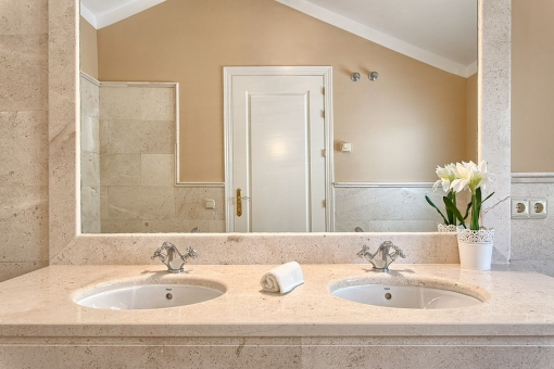 The noble bathroom offers a large mirror with marble elements