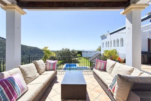 Überdachte Terrasse mit Sitzecke und Blick auf das Grundstück