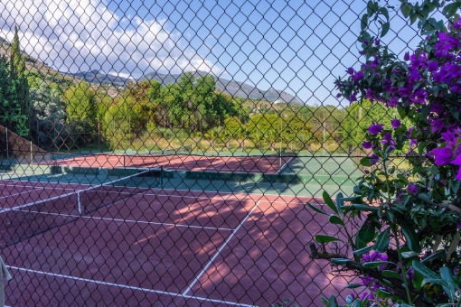 A tennis court is part of the outdoor area