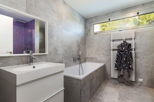 The childrens bathroom offers a shower, bath tub and natural light