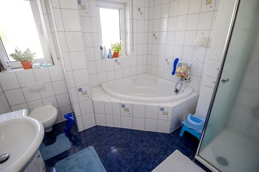 Bathroom with bathtub and shower on the upper floor