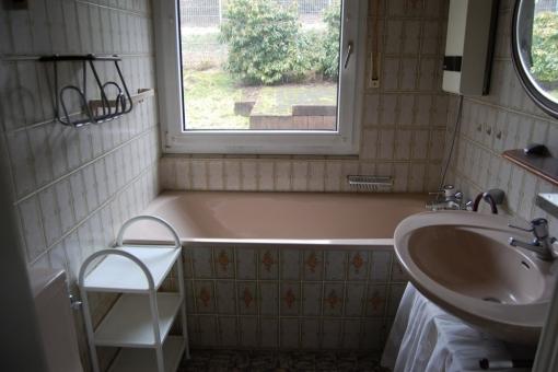 Badezimmer mit Badewanne und Blick in den Garten